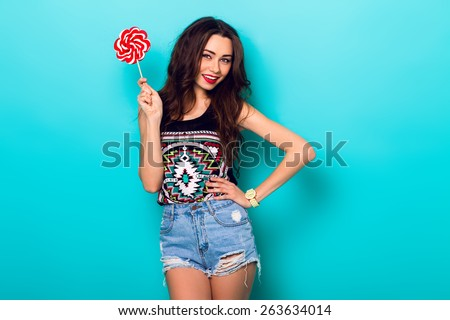 Studio closeup colorful portrait of young sexy funny fashion  girl posing on blue wall background in summer style outfit with red lollipop wearing  blue jeans and boho t-short. - stock photo