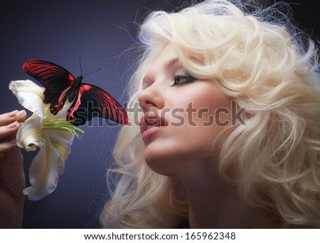 Studio closeup floral portrait of beautiful blonde with blue eyes holding white flower and tropical butterfly
