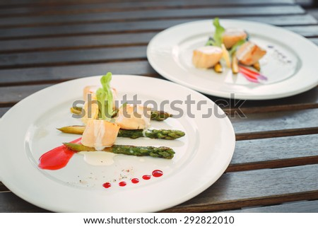 Studio closeup of seared scallops, garnished with pea shoots and - stock photo