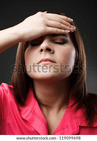 Studio closeup portrait of a young woman with strong migraine - stock photo