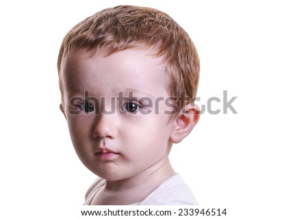 Studio closeup portrait of little baby boy with serious face looking inquisitive, isolated on white background - stock photo