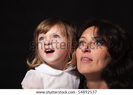 Studio closeup portrait of wondering happy mother with cute little daughter