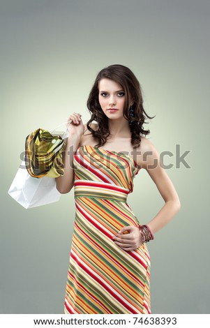 studio colorful image of a beautiful, young woman, holding a white shopping bag, looking proud and happy