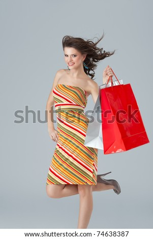 studio colorful image of a beautiful, young woman, with wind in her hair, holding a few shopping bags, looking very happy
