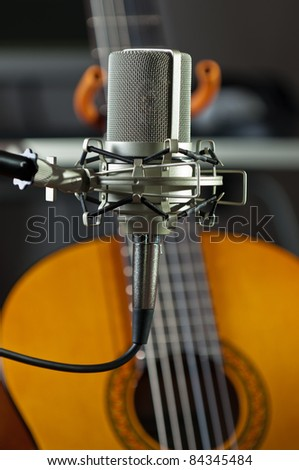 Studio condenser mic with an acoustic guitar - stock photo