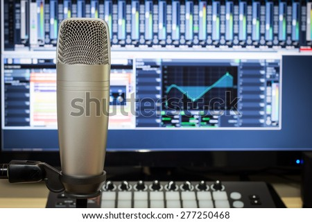 studio condenser microphone, midi synthesizer knob & digital mixer on screen monitor for computer music or broadcasting concept background - stock photo