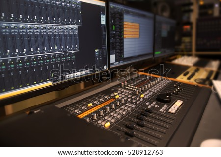 Studio control room with computer digital mixer and many studio equipment in blurry background.