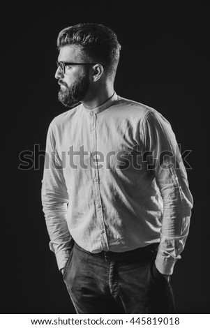 studio corporate portrait, bearded man with glass in isolated black, homogeneous