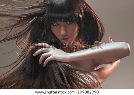 Studio creative portrait. Beautiful brunette with mess in in her hair looking into a camera - stock photo