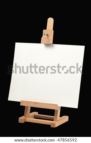 Studio easel with blank canvas isolated on black background