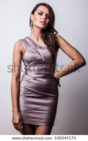 Studio fashion photo of beautiful young woman in elegance dress.
