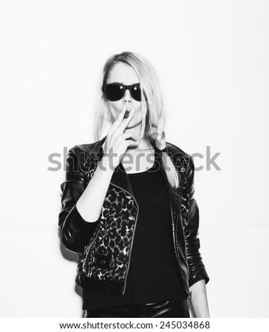 Studio fashion photo of Woman smoking cigar. Toned. White background, not isolated - stock photo