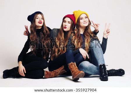 Studio fashion portrait of a group of three young beautiful model posing in winter leather shoes, warm clothes and colorful knitted caps. Friends having fun. Consumer concept, winter fashion - stock photo