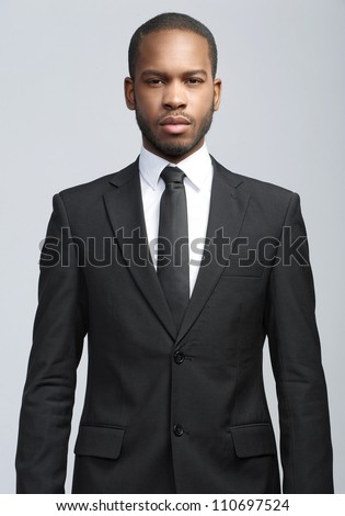 Studio fashion portrait of a handsome young African American businessman wearing a black suit and tie. Isolated on gray background - stock photo