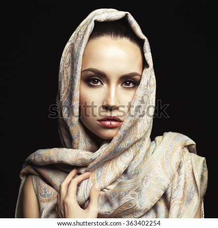 Studio fashion portrait of beautiful lady wrapped in a orient shawl - stock photo