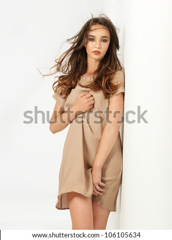 studio fashion portrait of sexy young woman, dressed in a beige dress - stock photo