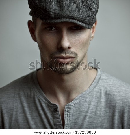 Studio fashion portrait of the handsome man in a cap. - stock photo
