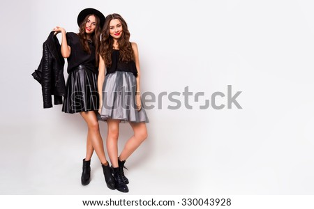 Studio fashion portrait of two elegant young women in fall stylish outfit posing in studio. Fashionable girls in skirts, bright make up, monochrome  clothes. Dress collection.  - stock photo
