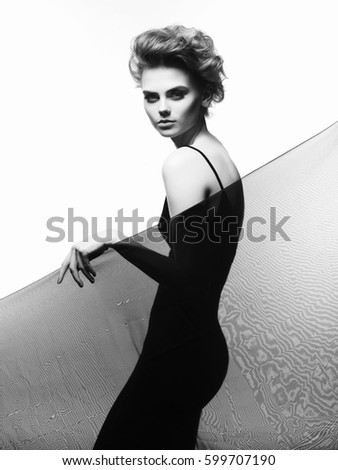 Studio fashion portrait of young beautiful lady in evening black dress. Elegant sexy woman with stylish haircut. Fashion female portrait of model with art smoky-eyes makeup.