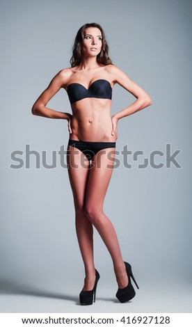 Studio fashion shot: a beautiful young girl wearing black lingerie and shoes - stock photo