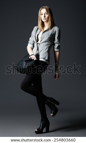 Studio fashion shot: a beautiful young woman in leggings and jacket, with bag in hand - stock photo