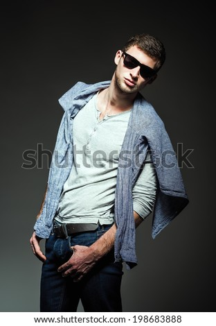 Studio fashion shot: a handsome young man wearing jeans, shirt and sunglasses - stock photo