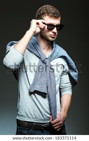 Studio fashion shot: handsome young man wearing jeans, shirt and sunglasses - stock photo