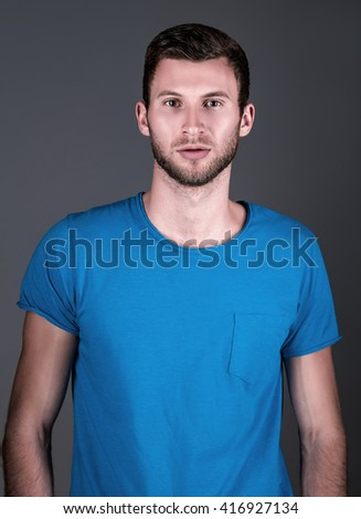 Studio fashion shot: portrait of a handsome young man in blue shirt  - stock photo