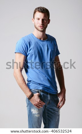 Studio fashion shot: portrait of a handsome young man wearing jeans and shirt  - stock photo