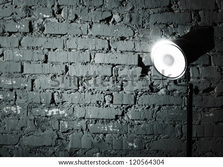 Studio flash near the gray damaged brick wall - stock photo