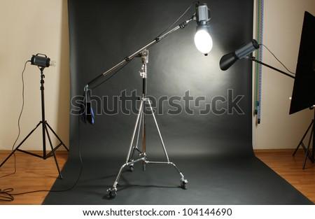 Studio flash with background reflector on black background - stock photo