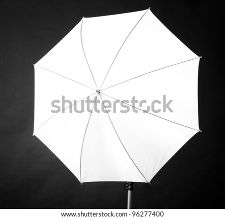 Studio flash with umbrella on grey background - stock photo