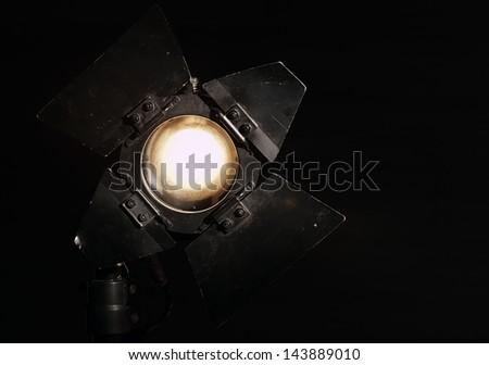 Studio floodlight on black background with warm tungsten light. - stock photo