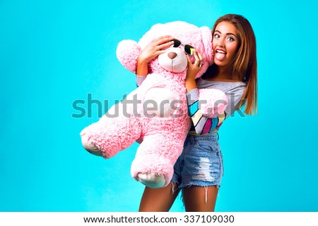 Studio funny portrait of pretty young woman playing with big fluffy teddy bear, mint background, sweet pastel colors. playing with sunglasses, holidays, present, happy crazy, fun, showing tongue. - stock photo