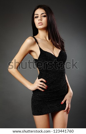 Studio glamour shot of a beautiful latin woman in black dress - stock photo
