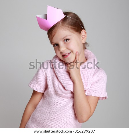 Studio image of a beautiful cheerful little girl in a pink knitted dress with a crown on his head on a gray background on Holiday