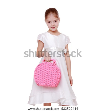 Studio image of a beautiful elegant little girl in a white dress holding a pink basket isolated on white