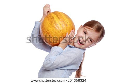 Studio image of a beautiful happy little girl in jeans holding a large orange pumpkin on a white background on Holiday/Little girl with a big pumpkin autumn harvest on Food - stock photo
