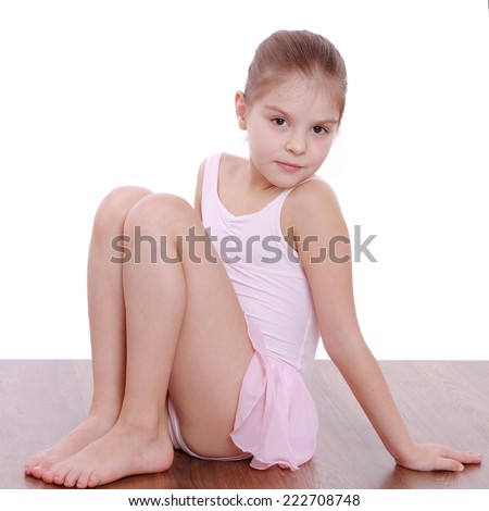 Studio image of a beautiful little girl in a pink leotard doing gymnastic exercises on the floor - stock photo