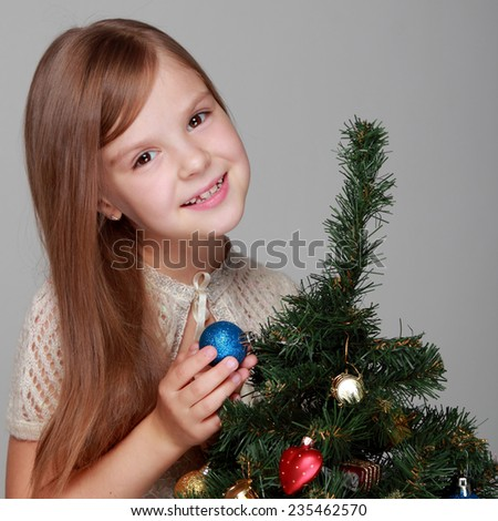 Studio image of a beautiful smiling little girl in a pink dress decorated Christmas tree in the New Year/Child near a decorated Christmas tree - stock photo