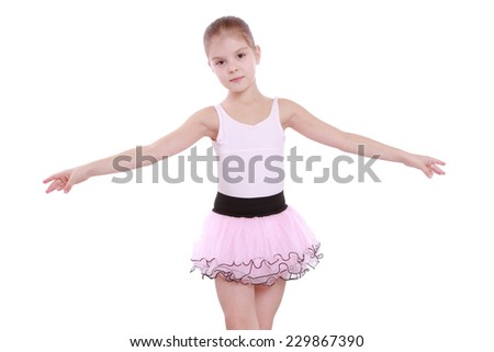Studio image of a charming smiling little ballerina in a pink tutu dancing isolated on white - stock photo