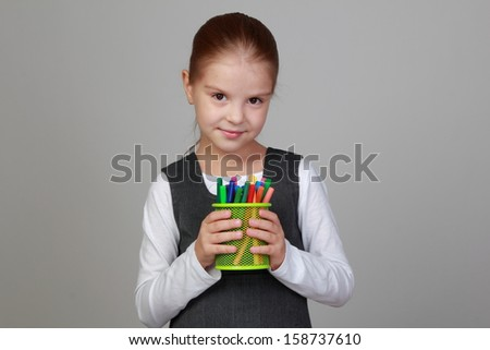Studio image of a charming young girl in a school uniform holding a lot of colored felt-tip pens on a gray background - stock photo