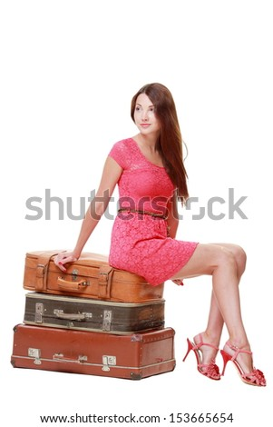 Studio image of a charming young woman in a summer dress sitting on old suitcase isolated on white on a travel theme
