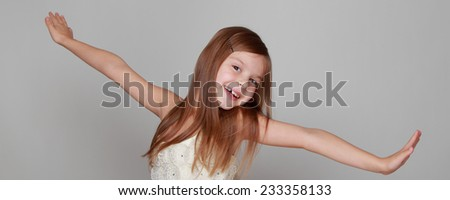 Studio image of a cheerful emotional little girl in a beautiful dress is dancing and having fun on a gray background