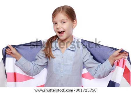 Studio image of a cute cheerful little girl with a happy smile, holding a large flag of England on a white background/Joyful girl with the flag the United Kingdom - stock photo