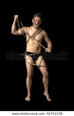 Studio image of a muscular man tied with ropes on black background. - stock photo