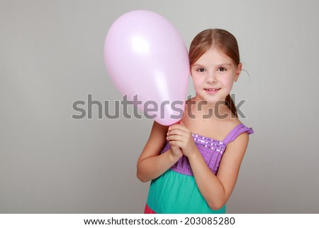 Studio image of a smiling cute little girl in a bright sundress holding balloons on gray background on Holiday