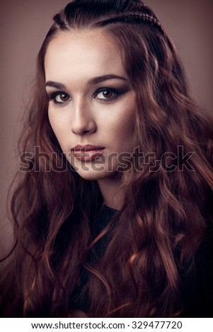 Studio image of a young female with curly hair - stock photo