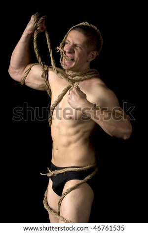 Studio image of a young man tied with ropes on black background. - stock photo