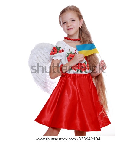 Studio image of emotional lovely little angel girl in a beautiful national Ukrainian suit holding a national flag isolated